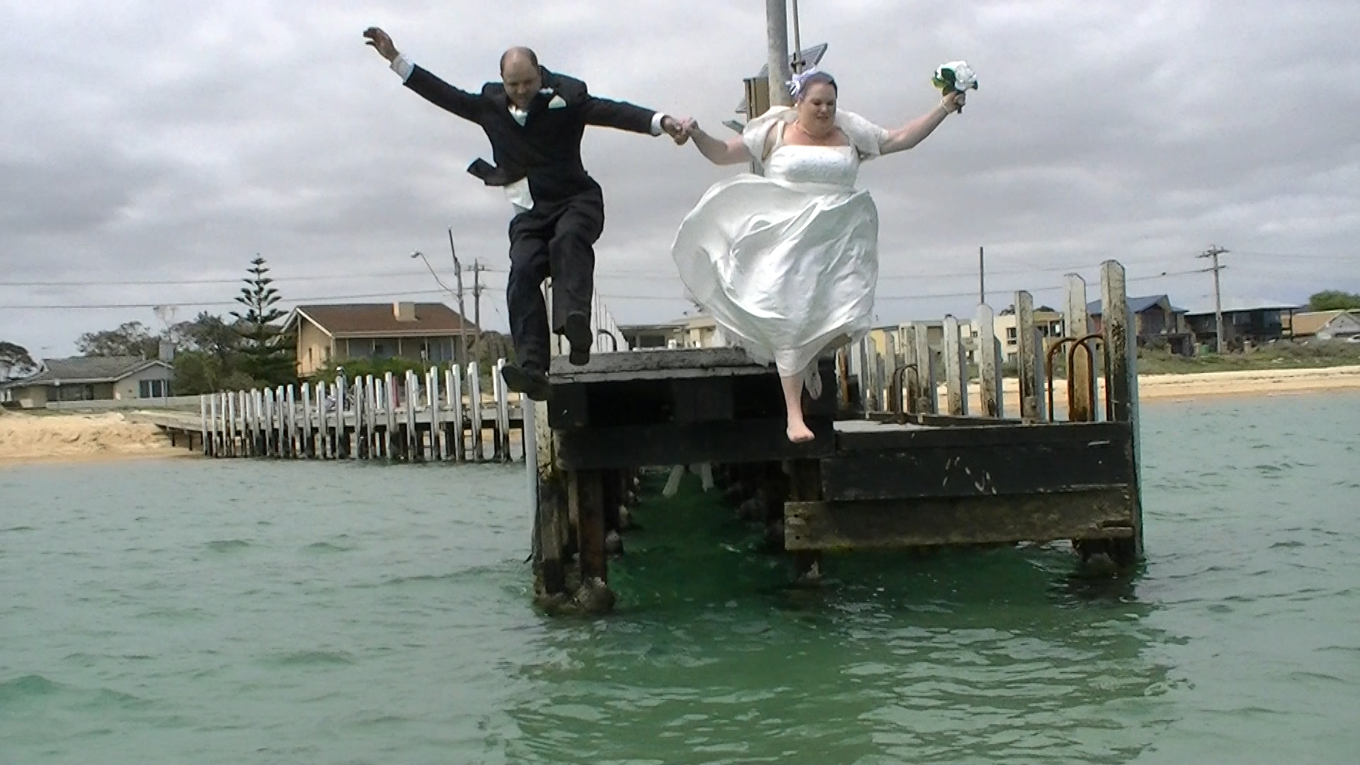 Wedding Couple jump into ocean